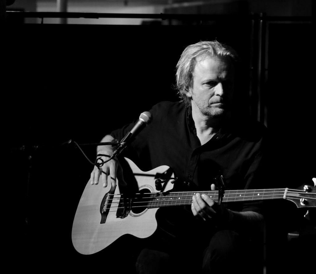 Svart-hvitt-fotografi av Mattis Kleppen med bassgitar.
