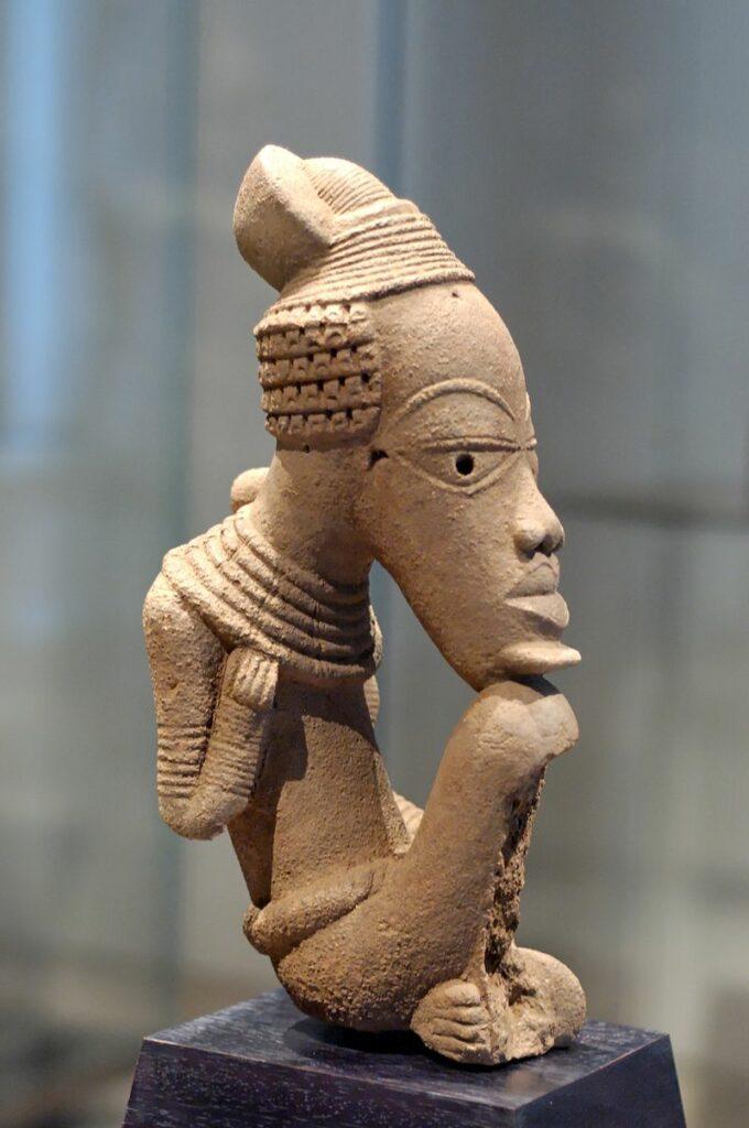 Fotografi av brun steinfigur av et menneske som hviler haken på kneet.