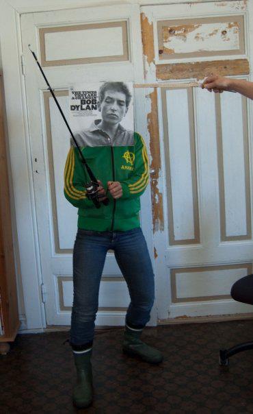 Foto av en person som står med støvler og fiskestang innendørs. Omslaget til The Times They are A-Changin' med Bob Dylan holdes opp foran ansiktet på personen. Omslaget viser hodet til Dylan, og effekten er at det ser litt ut som det er Dylan som står der.