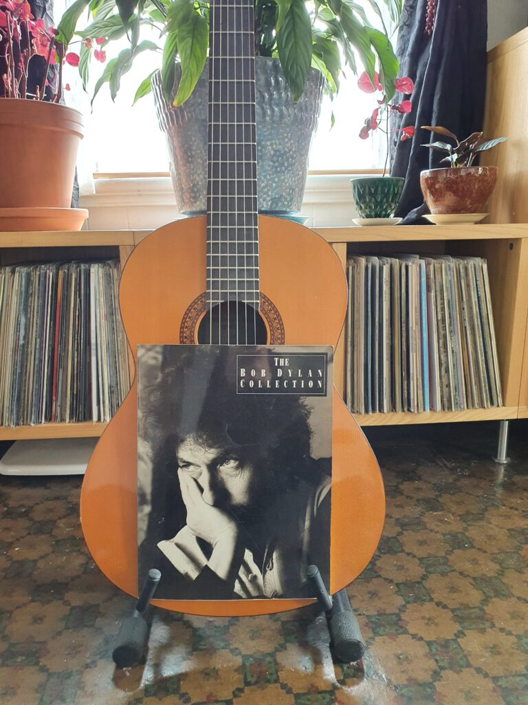 Fotografi av en gitar og en bok med tittel The Bob Dylan Collection.