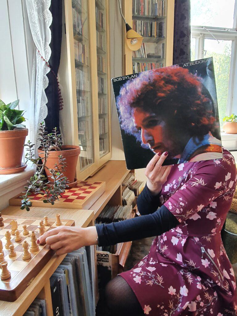 Fotografi av en kjolekledt person som spiller sjakk, med omslaget til Bob Dylan at Budokan foran hodet sitt slik at det ser ut som Dylan som sitter der.